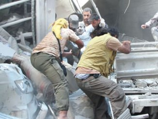 Syrian men evacuate a victim from the rubble of a building following an airstrike on the rebel-held northwestern city of Idlib. PHOTO: CNN