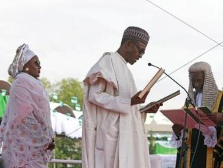 Chief Justice of Nigeria Mahmud Mohammed swears in Muhammadu Buhari (C) as Nigeria's president while Buhari's wife Aisha looks on at Eagle Square in Abuja, Nigeria May 29, 2015. REUTERS/Afolabi Sotunde