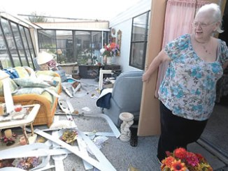 An American woman, Cherie Monroe, stands in the sunroom of her home in the aftermath of Hurricane Matthew in Port Orange, on Sunday. PHOTO: REUTERS.