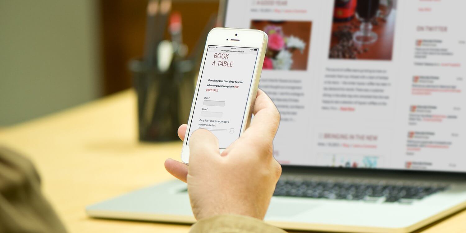 A photo of a man's hand holding an iPhone displaying the Naturally Chinese website booking form –Tribus Creative – website and marketing strategies for small business