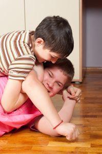 Two teenage boys wrestling on wooden floor