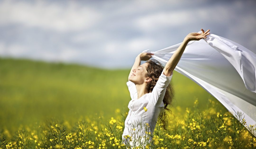Young happy woman standing in yellow rapeseed field holding a wh