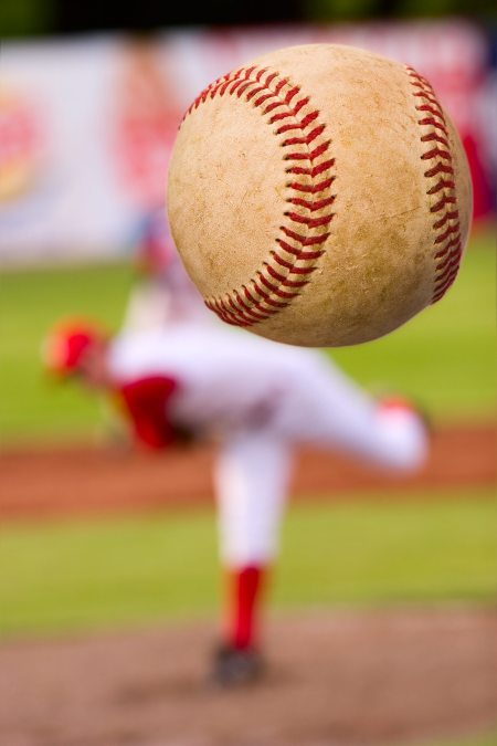 A baseball player pitching (focus on the ball)