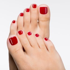 Closeup photo of a beautiful female feet with red pedicure isola