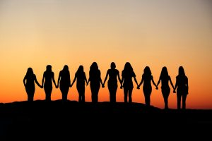 Sunrise silhouette of 10 young women walking hand in hand.