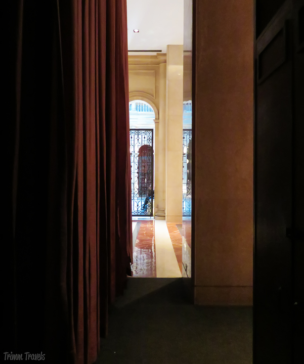 peeking down secret hallway into grand lobby of a hotel in New York City
