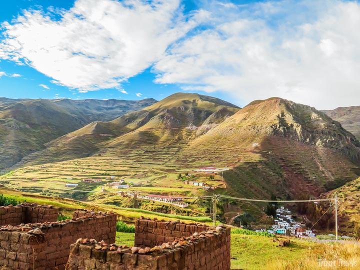 hills with brick fence and small village cusco region peru