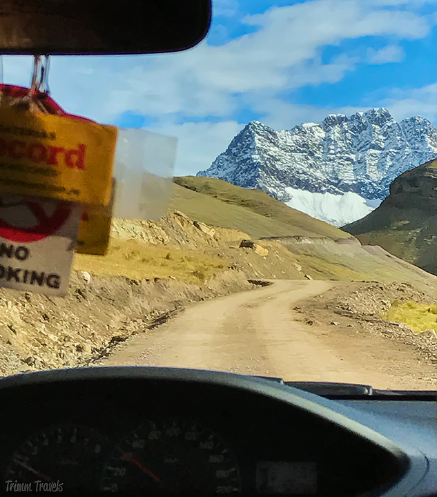 looking through the front windshield of the car at snowy mountain cusco region peru
