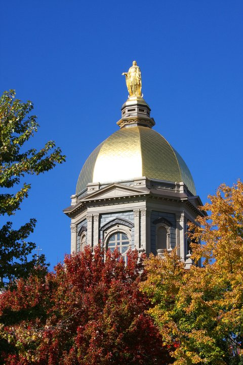 Golden Dome at the University of Notre Dame, Indiana against a blue sky with colorful fall trees