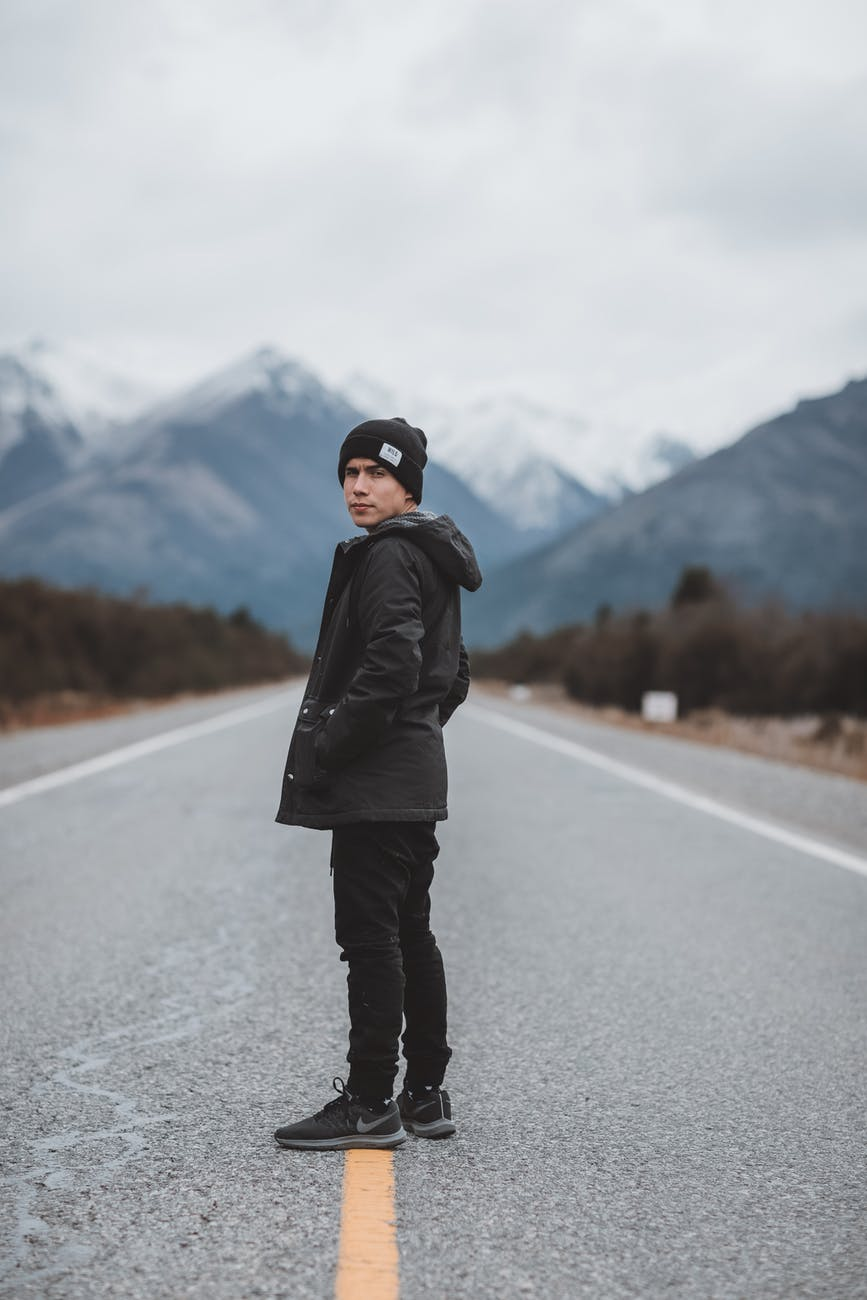 traveling man on empty road in mountains