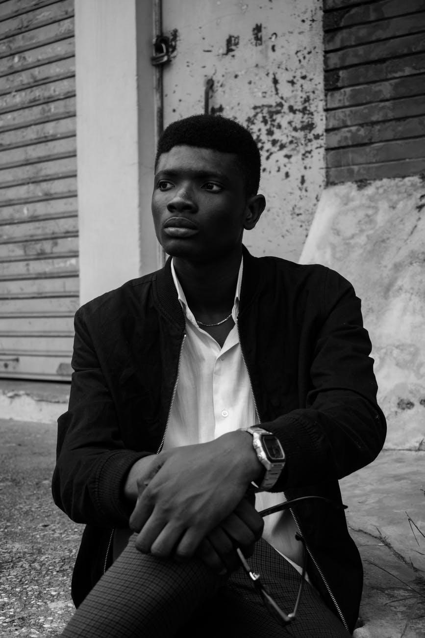 stylish black man sitting on street
