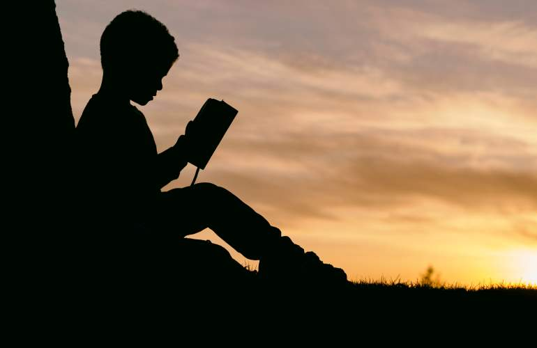 Kid sitting reading a book by a tree at sunset