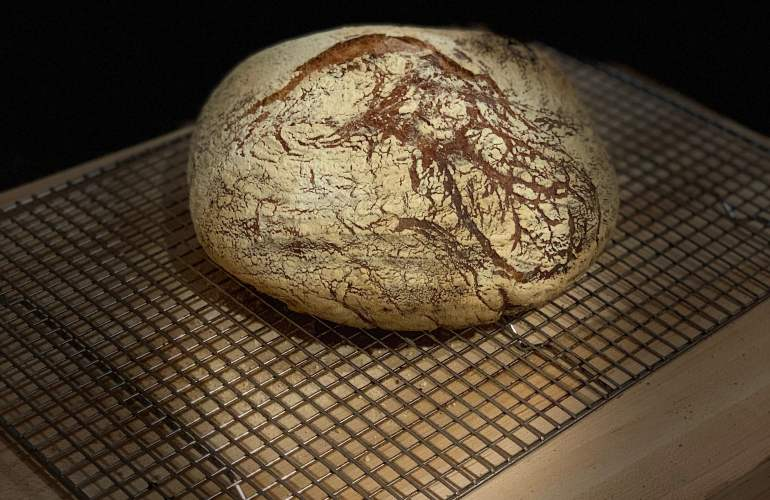 Finished rustic bread on a cooling rack.