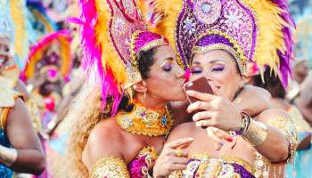 Two women kissing and taking a selfie.