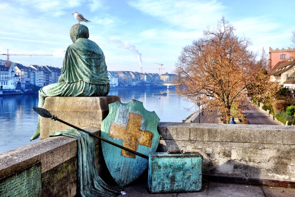 Helvetia thinks about her travels at the border of the Rhein in Basel