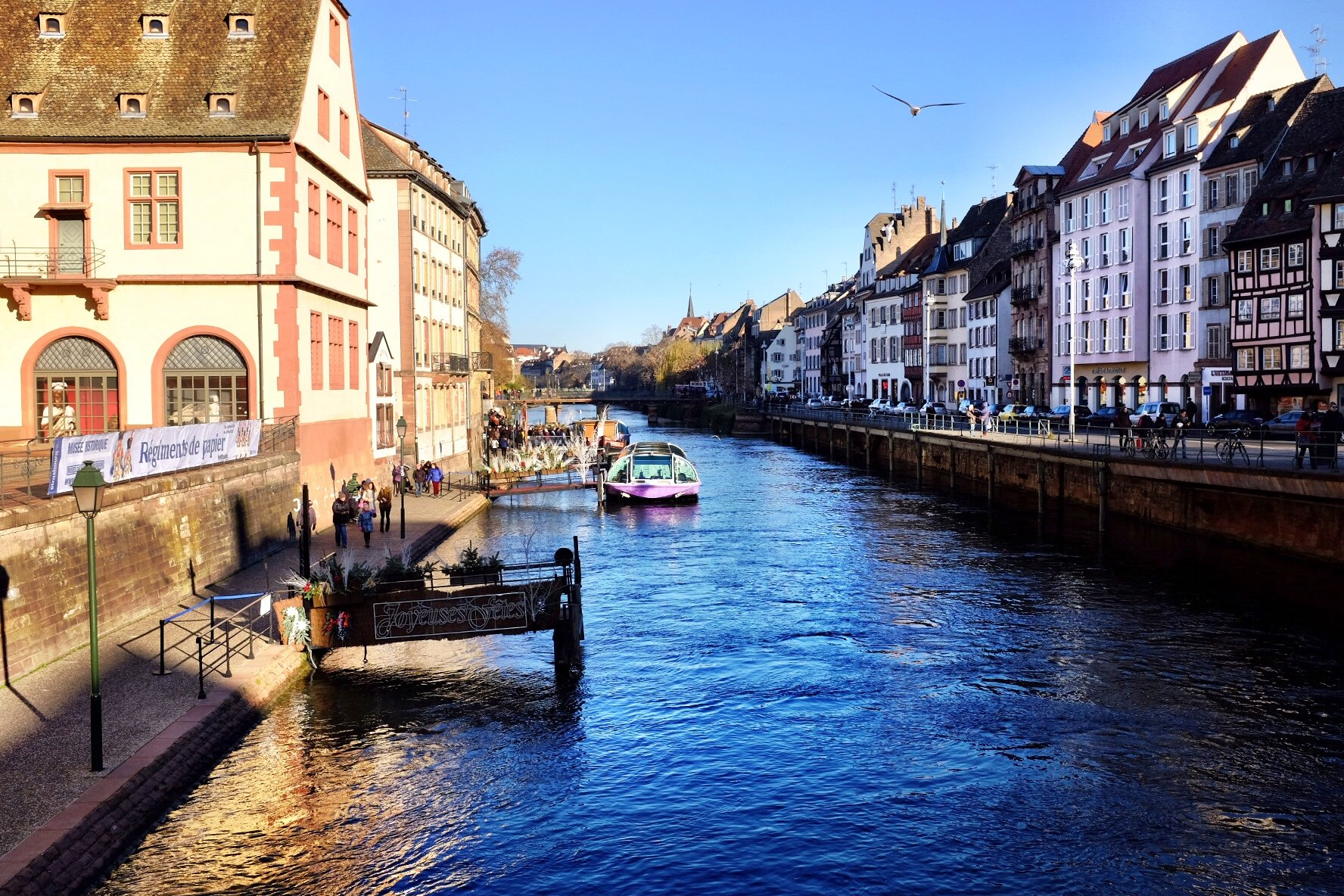 The river Ill in Strasbourg. Old houses at the boarder and a boat in the water.