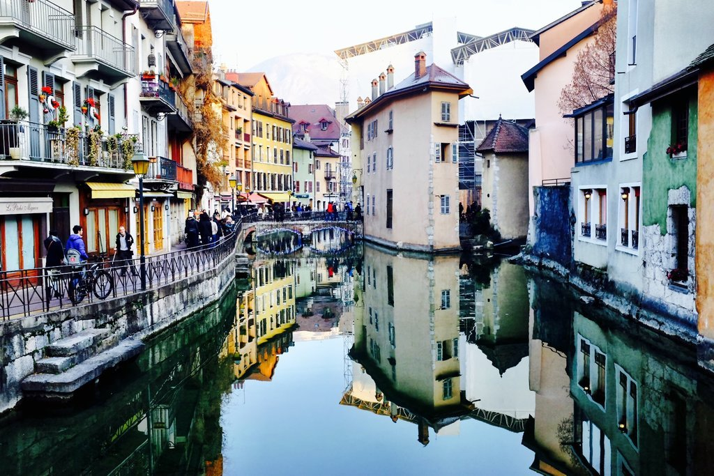 Old historical buildings reflecting in river Thiou in Annecy in winter