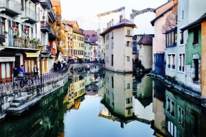 Annecy picture gallery. Old historical buildings reflecting in river Thiou in Annecy