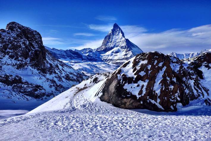 Beautiful snowy landscape with rock formations in the foreground and the Matterhorn in the background