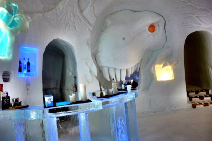 A bar inside of an igloo with a head of a Tyrannosaurus rex carved out of snow. Near Zermatt