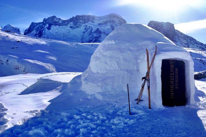 An igloo with some skis leaning to it. In the background are the Alps