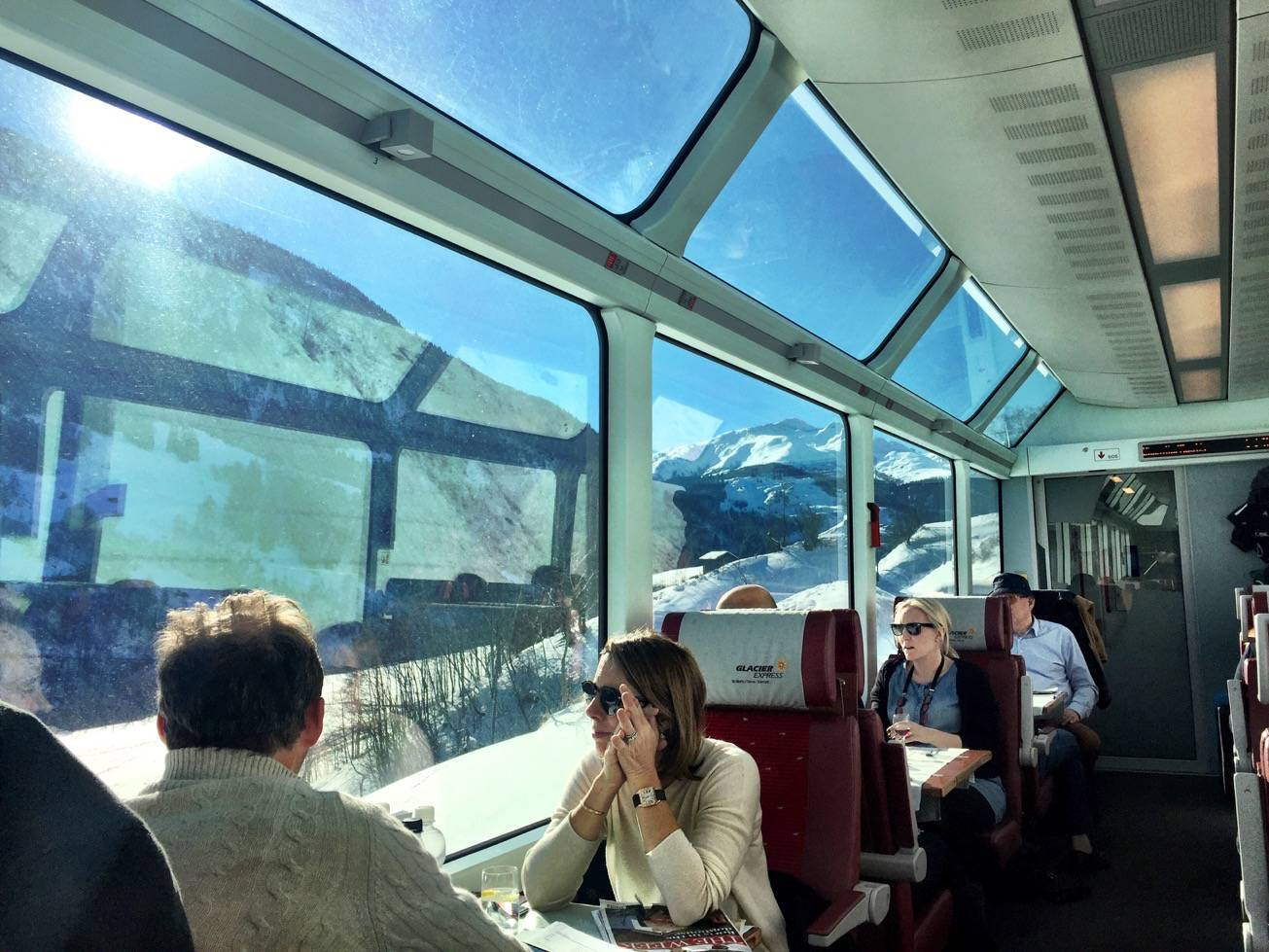 People sitting inside the Glacier Express and enjoying the view of the snowy mountains outside
