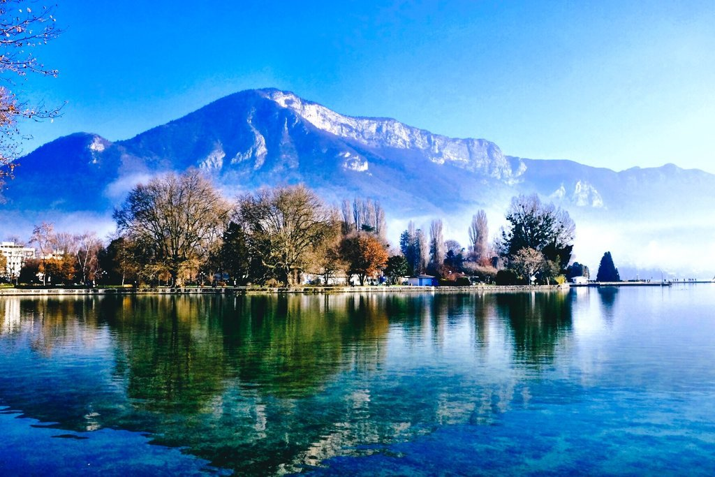 The mountain and trees in Annecy are reflected in the lake