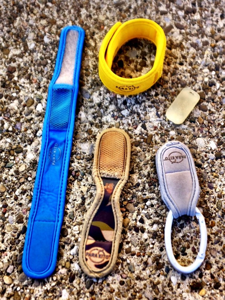 A blue unfolded Parakito wristband, a yellow folded Parakito wristband, a grey folded Parakito pouch on a carbine, a camouflage colored unfolded Parakito pouch and a refill. Efficent against mosquitos