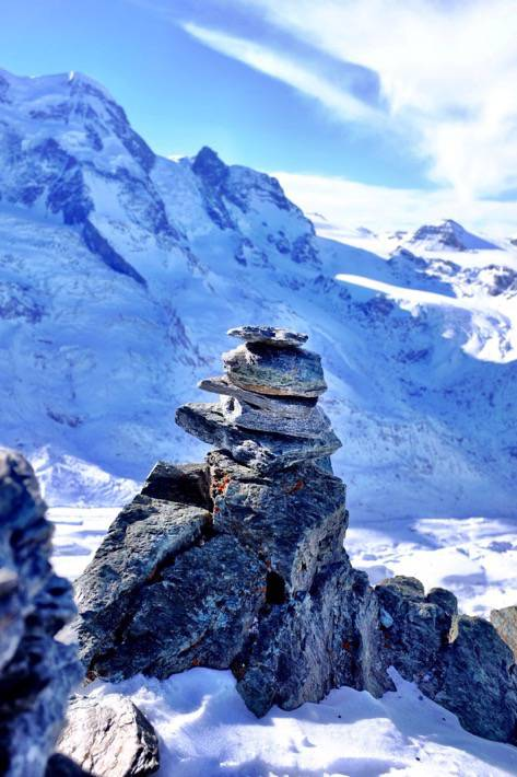 A tower build of stones and the alps in the background. In Zermatt