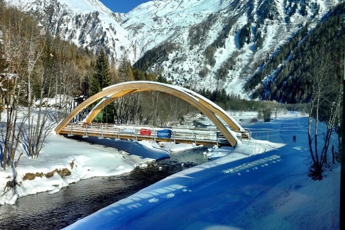 A wooden bridge with snowy mountains in the background Glacier Express