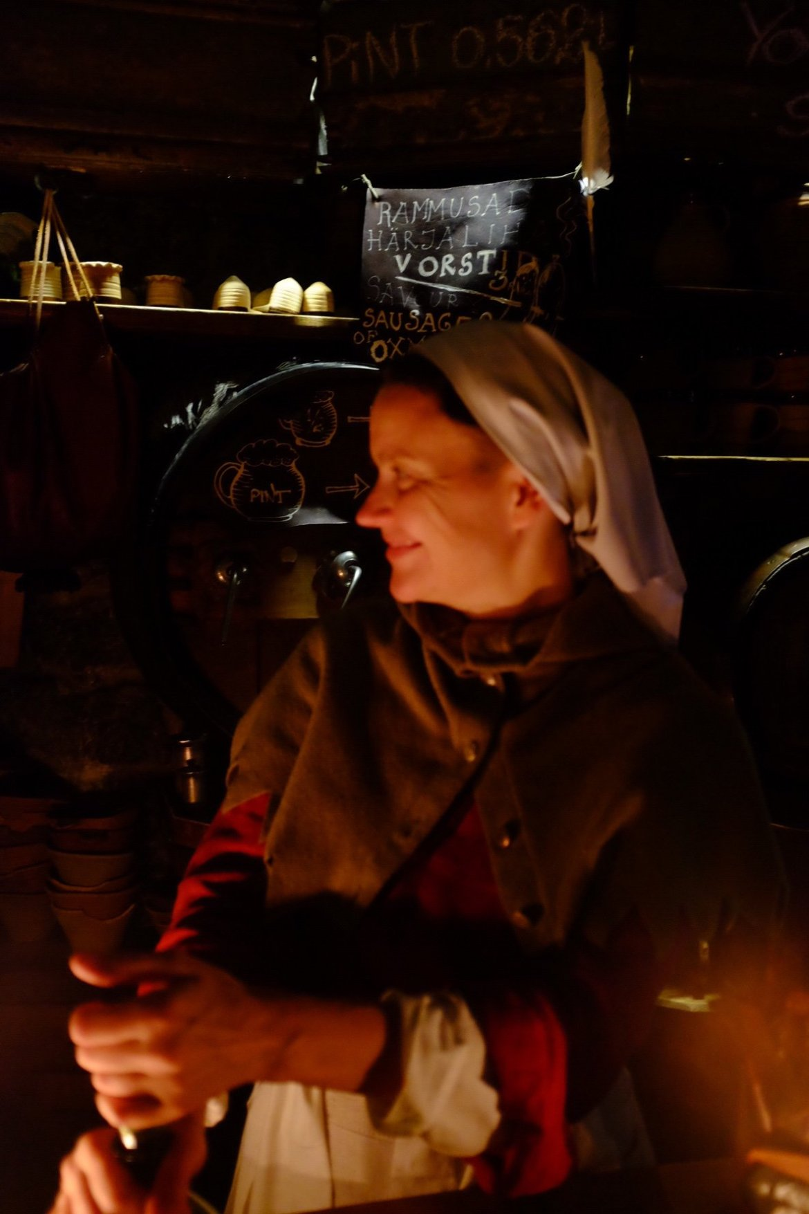A lady in medieval clothes working behind the bar in the Draakon in Tallinn