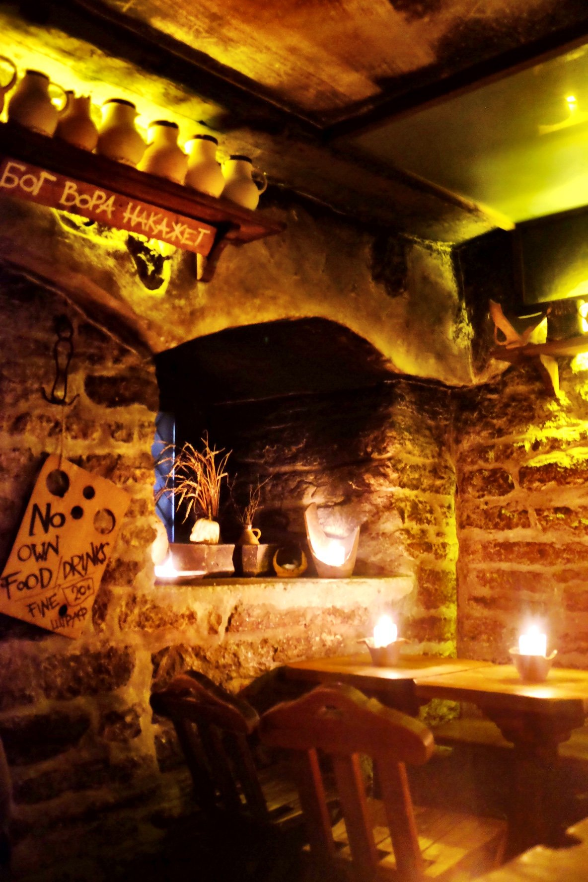 The inside of the Draakon. The room, made of stone bricks, is illuminated by candles and there is a medieval decor in form of ceramic mugs and plants. Found in Tallinn