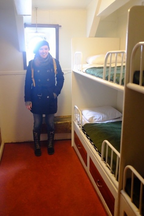 Sarah stands in a 6 person bedroom in the Icebreaker who's exhibited at the Seaplane Museum in Tallinn