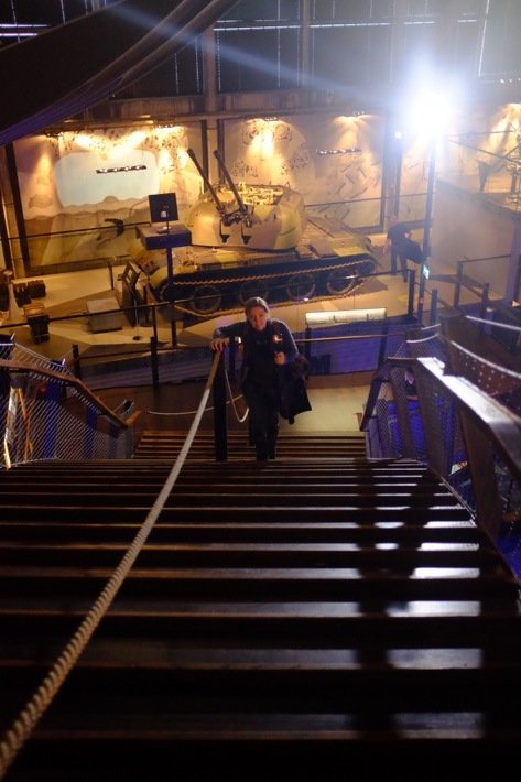 Sarah climbing up the steep steps of the bridge at the Seaplane Museum in Tallinn