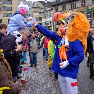 Basel Fasnacht Waggis in traditional costume giving sweets to a child