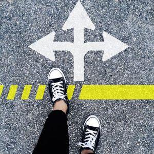 Feet wearing Converse standing at crossroads