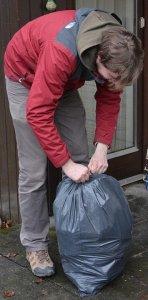 man packing something in a trash bag