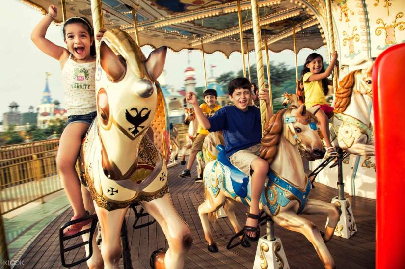 kids sit on a carousel at Imagicaa Theme Park