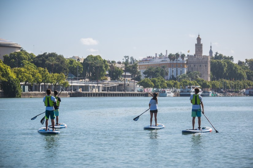 people are surfing paddle on Guadalquivir river