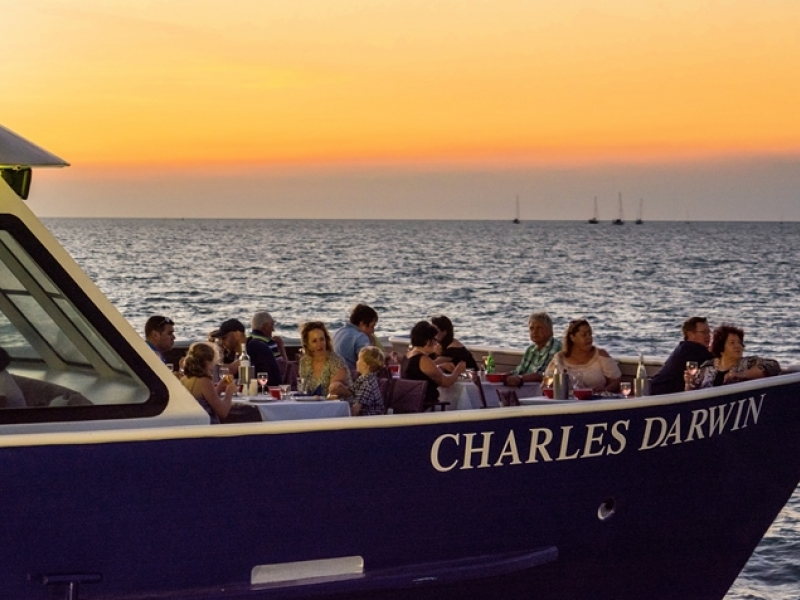 people are sitting on the sundeck of Charles Darwin Dinner Cruise