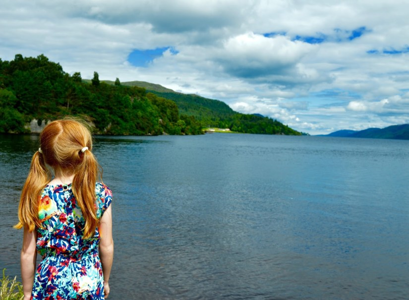 a kid is standing at loch ness lake