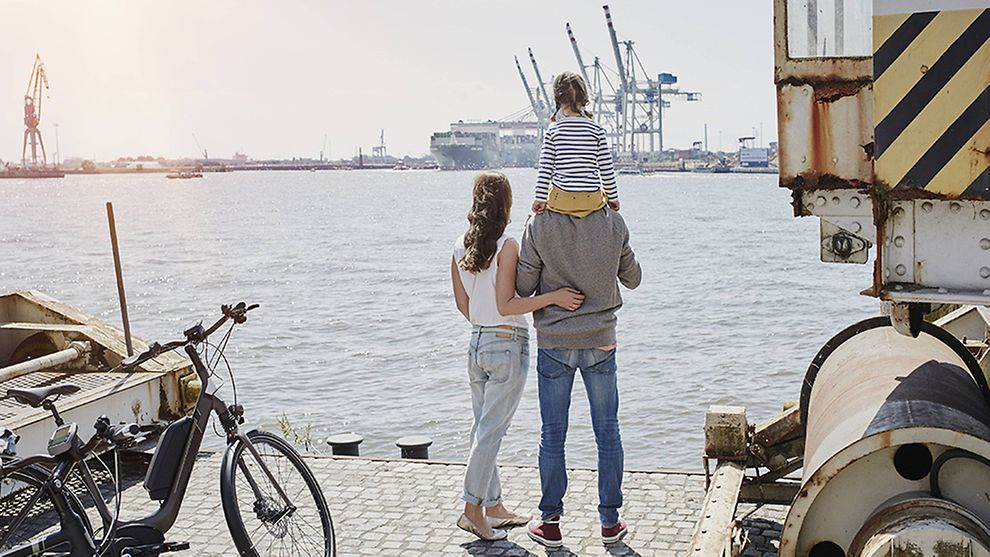 a man carries his kid and stand next to his wife at port of Hamburg