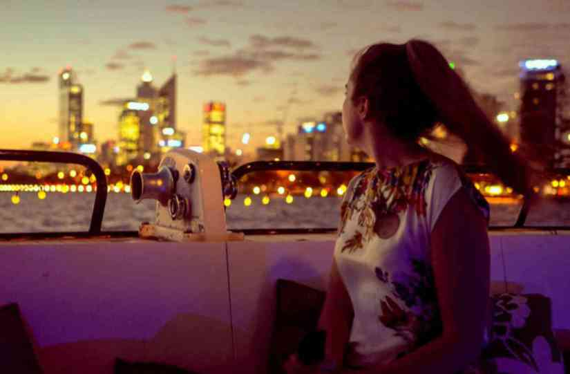 a woman sits on the Swan River Twilight Cruise in Perth