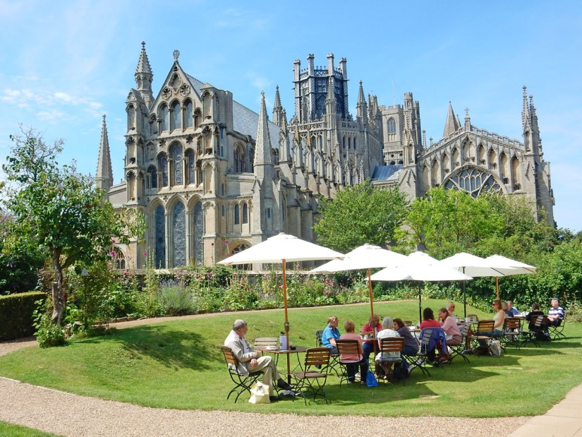 people are sitting in the garden in font of Ely Cathedral