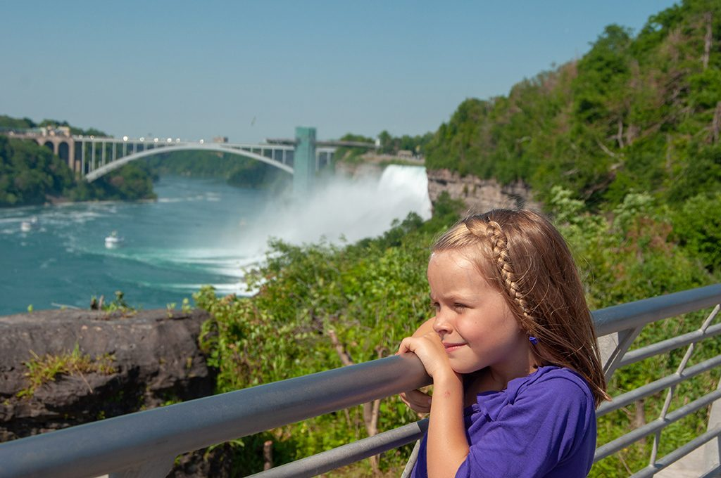 a girl is standing in font of Niagara Falls