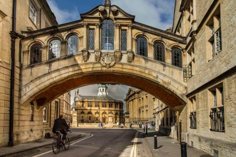 a man ride a bike under the Bridge of Sighs