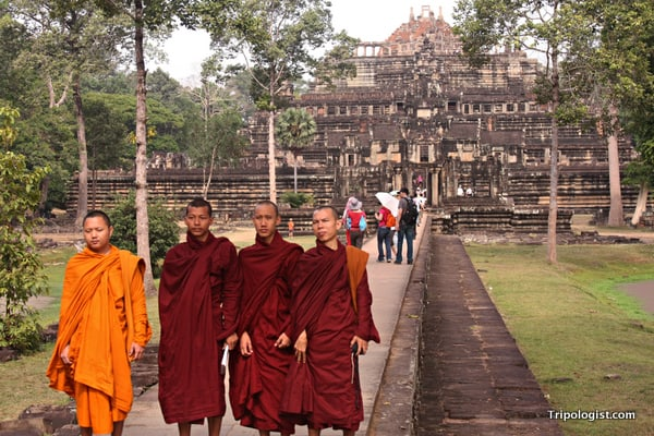 Four Buddhist monks pose in front of a temple at Angkor Thom.