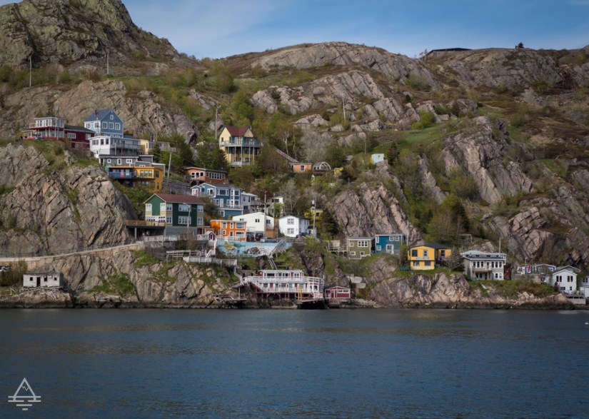 View of buildings on the side of a cliff beside the harbour