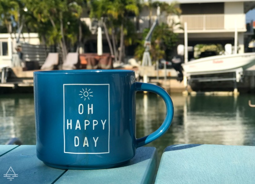 Coffee cup that says OH HAPPY DAY in front of the canal