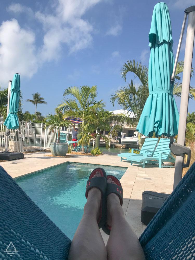Legs on hammock with pool and umbrella
